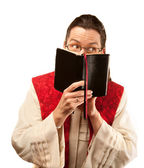 Pastor looking out from behind Bible — Stock Photo
