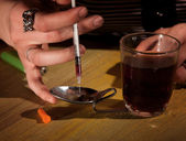 Drawing black tar heroin into a needle — Stock Photo
