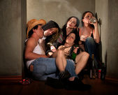 Partygoers surrounded by booze bottles in a hallway — Stock Photo