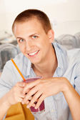 A young man holding a frozen beverage. — Stock Photo