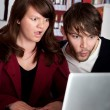 Stock Photo: Womand mstaring with shock at laptop