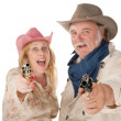 Couple in western wear pointing pistols — ストック写真
