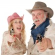 Couple in western wear pointing pistols — Stok fotoğraf
