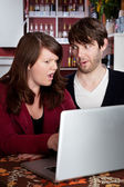Woman and man staring in disbelief at a computer laptop — Stock Photo