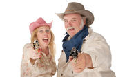 Couple in western wear pointing pistols — Stock Photo