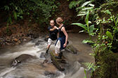Woman helping man cross Costa Rican river — Stock Photo