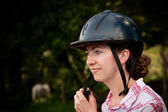 Costa Rican tourist putting on equestrian helmet — Stock Photo