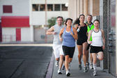 Group of friends runs downtown. — Stock Photo