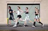 Foursome runs in the city for exercise. — Stock Photo