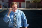 Good-looking guy excitedly talks on cell phone — Stock Photo