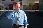 Pleased, good-looking guy talks on cell phone. — Stock Photo