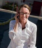 Beautiful woman smiles as she talks on cell phone. — Stock Photo