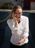 Shocked and amazed woman talks on cell phone — Stock Photo