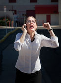 Beautiful woman yells into cell phone — Stockfoto
