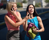 Beautiful women talking on phones in city — Stock Photo