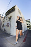 Woman out for a morning run downtown — Stock Photo