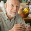 Senior man at home counting money — Stock Photo