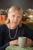Depressed senior woman with mug — Foto Stock