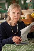 Senior woman with many bills — Stock Photo