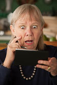 Senior woman with checkbook — Stock Photo