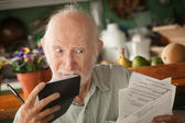 Senior man with many bills — Stock fotografie