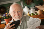 Senior man with many bills — Stockfoto