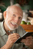 Senior man with checkbook — Stock Photo