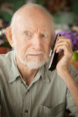 Grumpy senior man on telephone — Stock Photo