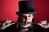 Woman in top hat biting whip — Stock Photo