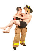 Sexy firefighter rescues a handsome man — Stock Photo