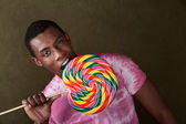 Young Man Bites Into a Giant Lollipop — Stock Photo