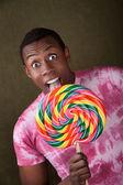 Man Licks Giant Candy Sucker — Stock Photo