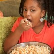 Stock Photo: Little Girl Eats Popcorn