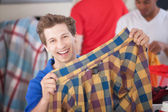 Grinning Man Holding Shirt — Stock Photo