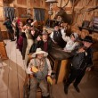 Customers in Old Saloon Toasting Drinks — Stock Photo #40888505