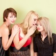 Attractive teen girls sharing secrets — Stock Photo