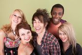Five laughing urban teens in front of green wall — Stock Photo