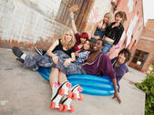 Fun loving group of crazy teen punks sit in a blue inflateable p — Zdjęcie stockowe