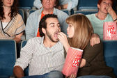 Woman Feeds Boyfriend at Movie — Zdjęcie stockowe