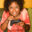African-American woman plays video game — Stockfoto