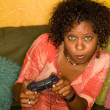 Постер, плакат: African American woman plays video game