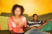 African-american woman and teen sit on sofa — Stock Photo