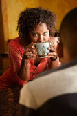 African-American woman talks with male in kitchen — Stock Photo