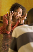 African-American female and male talk in kitchen — Stock Photo