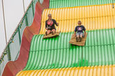 Kids on carnival slide at state fair — Stock Photo