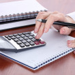 Women hands with pencil, notebooks and Calculator on wooden table — Stock Photo #10347413