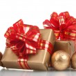 Beautiful golden gifts with red ribbon and Christmas balls isolated on white — Stock Photo #10730436