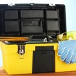 Open yellow tool box with tools on blue background close-up — Стоковое фото #11999117