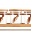 Stock Photo: Empty glass jars for spices with spoons on wooden shelf isolated on white