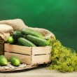 Fresh cucumbers in wooden box, pickles and dill, on green background — Stock Photo